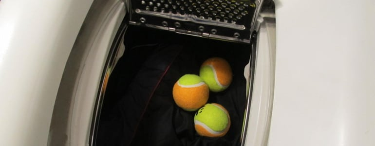 Daunenjacke mit Tennisbaellen trocknen