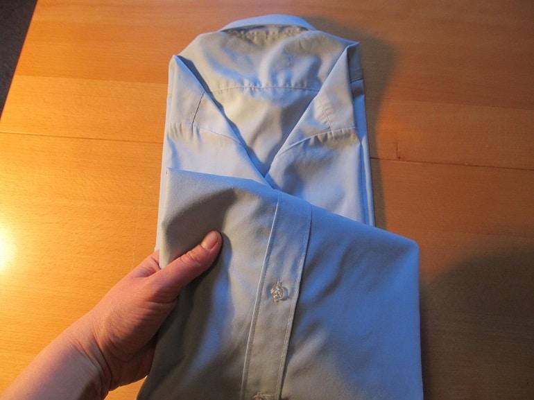 die untere Haelfte des Hemdes nach oben falten